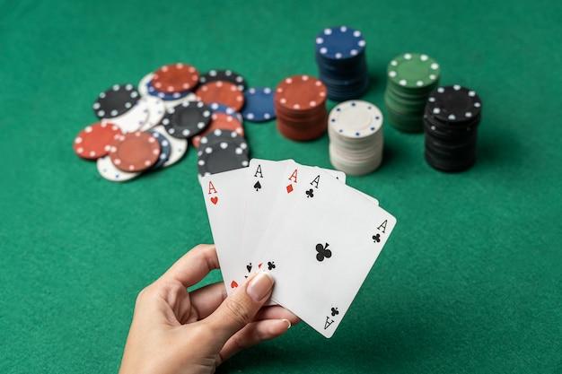 Pilha de fichas e mão de mulher com quatro ases na mesa. conceito de jogo de poker Foto Premium