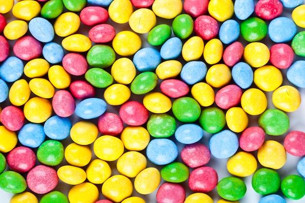 Pilha de fundo de doces coloridos de chocolate delicioso arco-íris Foto Premium