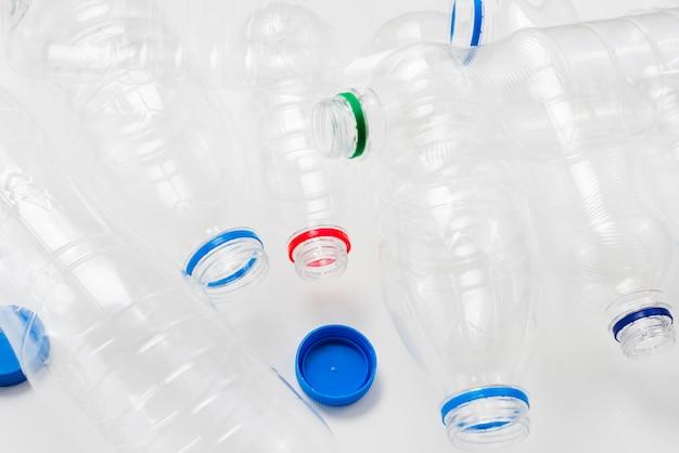 Pilha de garrafas plásticas e bonés em fundo cinza Foto gratuita