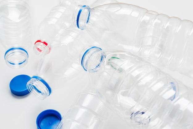 Pilha de garrafas plásticas vazias e bonés Foto gratuita
