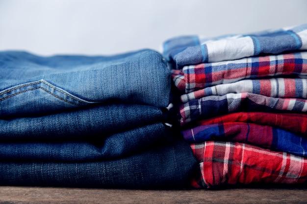 Pilha de jeans e camisas quadriculada Foto Premium