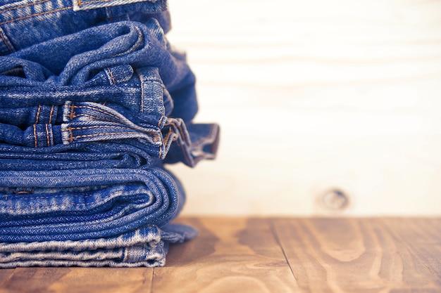 Pilha de jeans no revestimento de madeira velha, conceito de moda Foto Premium
