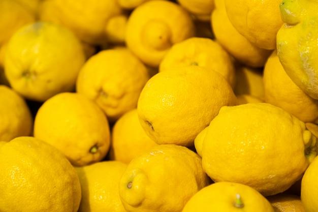 Pilha de limões amarelos maduros no mercado de verão para venda, para o fundo Foto Premium