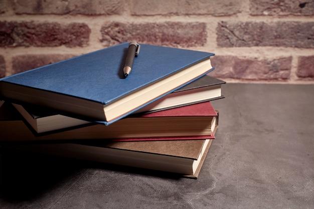 Pilha de livros de cores diferentes ao lado de uma caneta Foto Premium