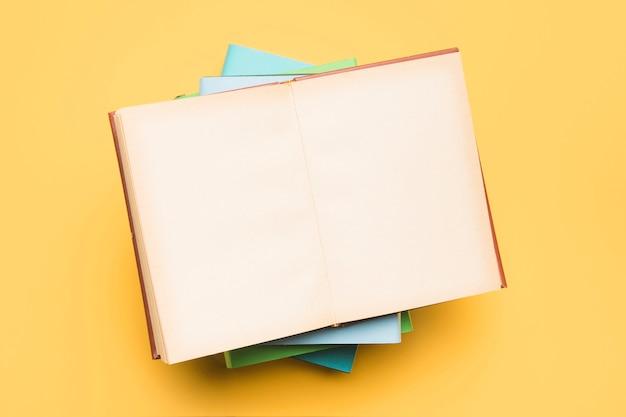 Pilha de livros e bloco de notas aberto com páginas em branco Foto gratuita