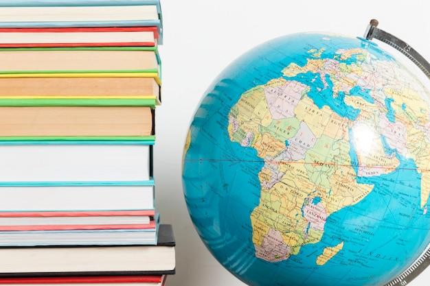 Pilha de livros e globo Foto gratuita