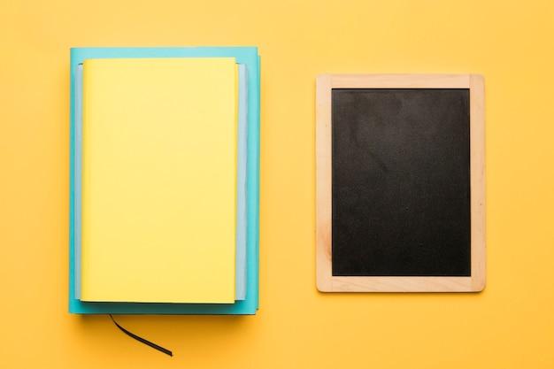 Pilha de livros e quadro negro sobre fundo amarelo Foto gratuita