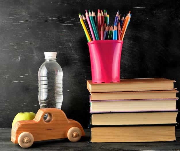 Pilha de livros e um copo de papelaria rosa com lápis de madeira multi-coloridas Foto Premium