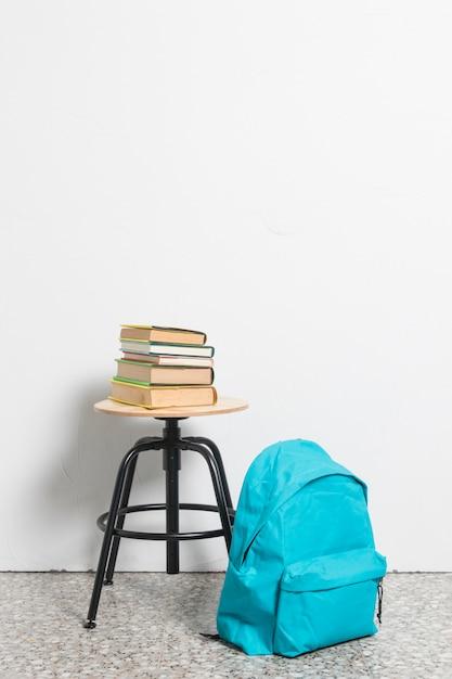 Pilha de livros na cadeira de fezes com mochila azul no chão Foto gratuita