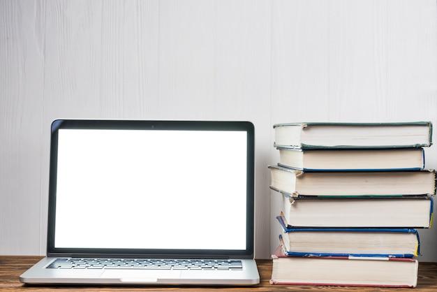 Pilha de livros perto do laptop Foto gratuita