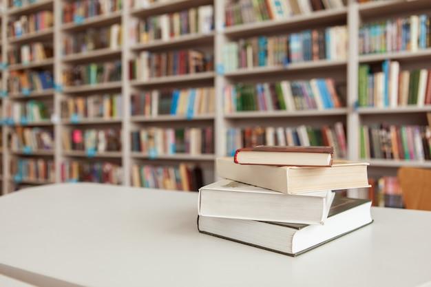 Pilha de livros sobre a mesa na biblioteca Foto Premium