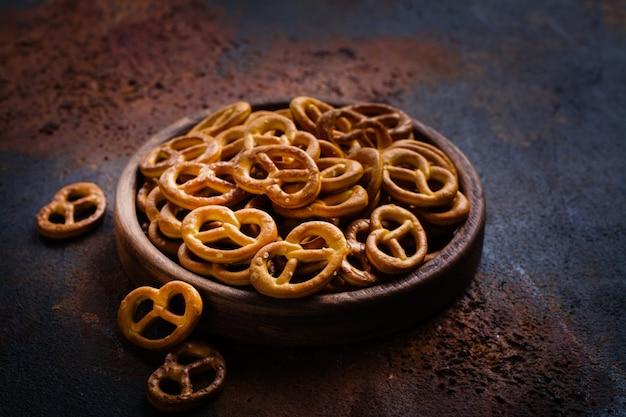 Pilha de mini pretzels na placa de madeira Foto Premium