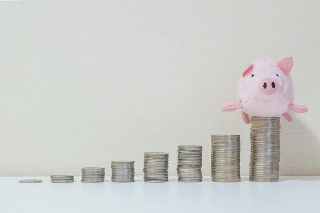 Pilha de moeda começar de baixo para alto com boneca de porco no topo no sucesso de salvar o conceito de dinheiro Foto Premium
