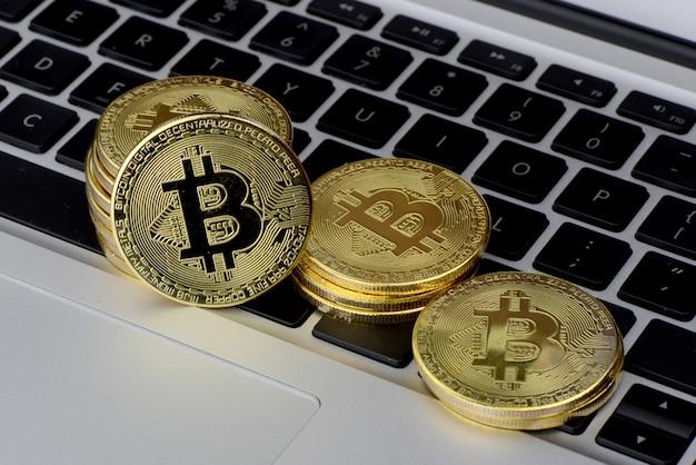 Pilha de moedas bitcoin no teclado do laptop Foto Premium