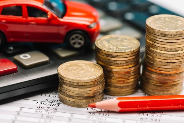 Pilha de moedas; calculadora; carro de brinquedo no relatório financeiro com lápis colorido vermelho Foto gratuita