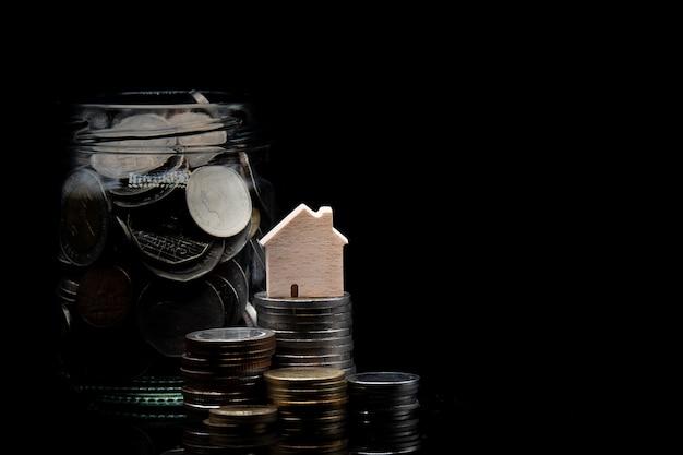 Pilha de moedas e limpar jarra com moeda com casa de madeira no fundo preto Foto Premium