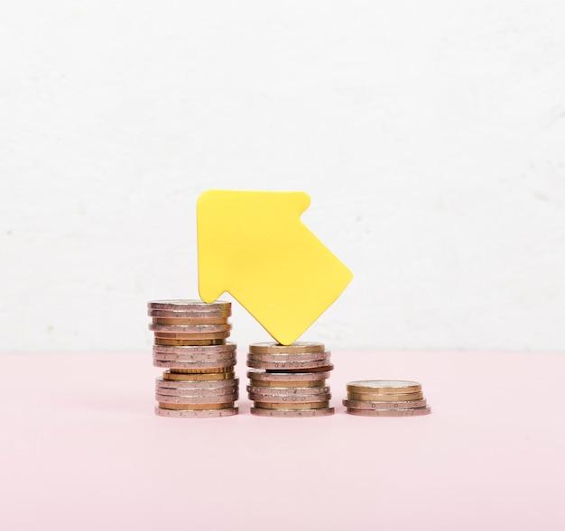 Pilha de moedas e seta apontando para cima Foto gratuita