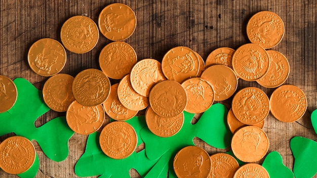 Pilha de moedas e trevos de papel na mesa de madeira Foto gratuita