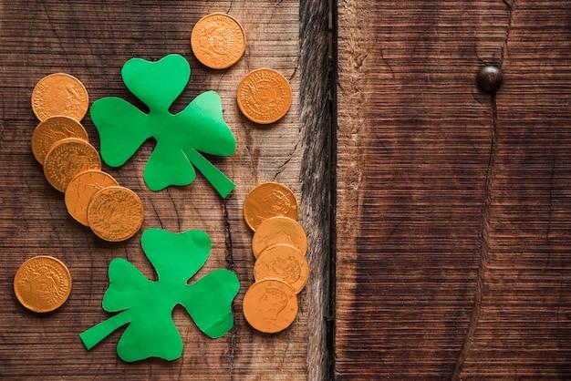 Pilha de moedas e trevos de papel verde na mesa de madeira Foto gratuita