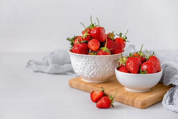 Pilha de morangos frescos em uma tigela de cerâmica Foto Premium