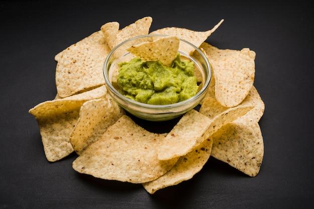 Pilha de nachos e molho na tigela Foto gratuita