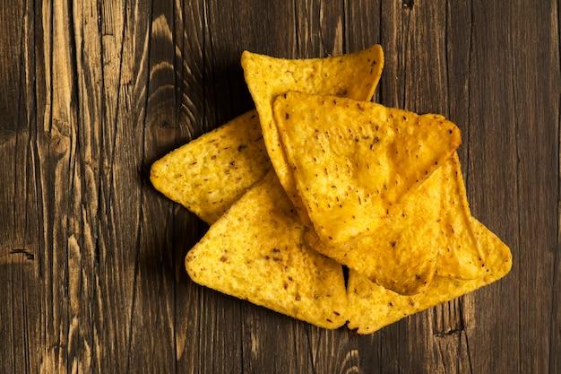 Pilha de nachos sobre mesa de madeira Foto Premium