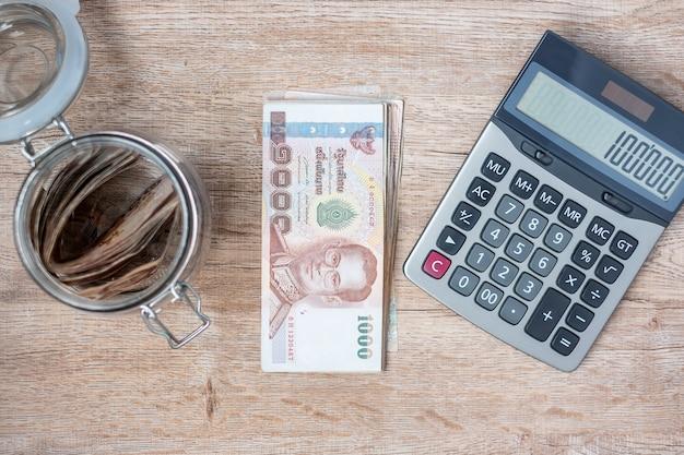Pilha de notas de baht tailandês e usando a calculadora. Foto Premium