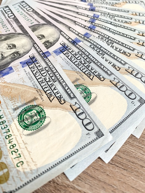 Pilha de notas de cem dólares na mesa de madeira Foto Premium