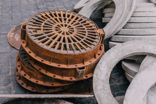 Pilha de novas escotilhas de concreto redondas industriais para o sistema de esgotos. escotilha de esgoto Foto Premium
