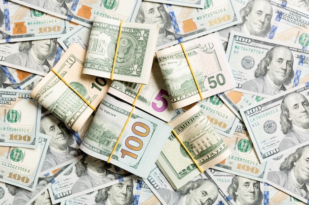 Pilha de pacotes de notas de dólar dos eua. notas de cem dólares com pilha de dinheiro no meio. vista superior dos negócios com copyspace Foto Premium