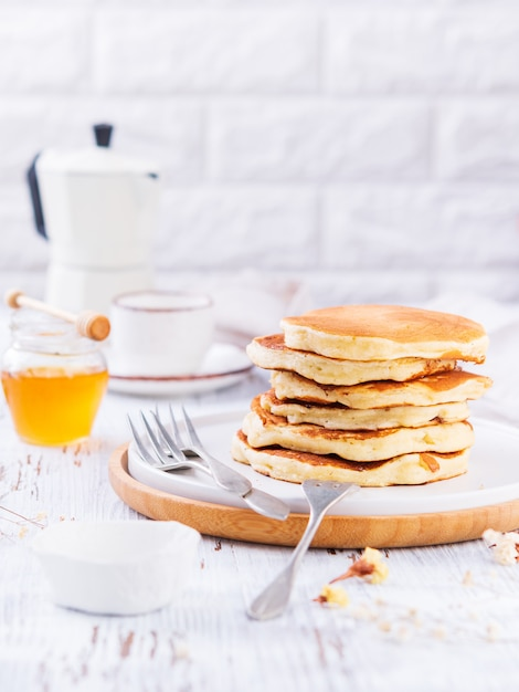 Pilha de panquecas deliciosas douradas, mel e café Foto Premium