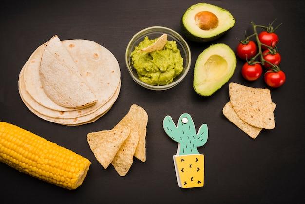 Pilha de pita perto de legumes e molho de guacamole com nachos Foto gratuita