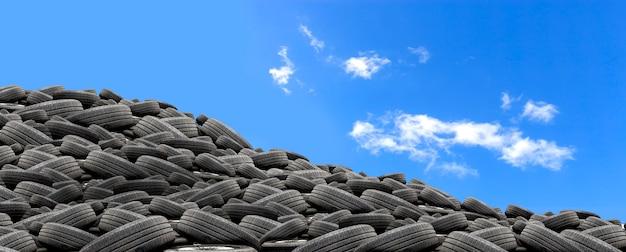 Pilha de pneus de borracha usados com mais de luz no fundo do céu azul Foto Premium