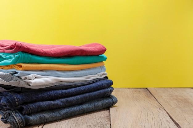 Pilha de roupas coloridas na mesa de madeira amarelo fundo Foto Premium