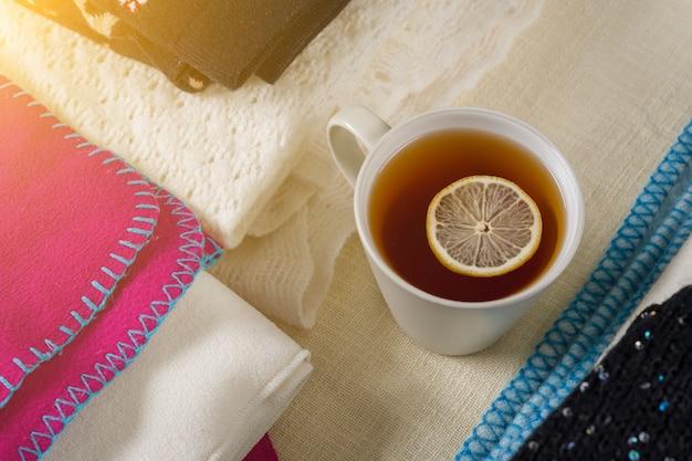 Pilha de roupas de lã quentes com uma xícara de chá Foto Premium