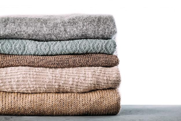 Pilha de roupas de malha de inverno na mesa Foto Premium