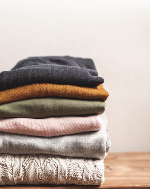 Pilha de roupas outono lanxess em fundo de madeira, camisolas, malhas Foto Premium