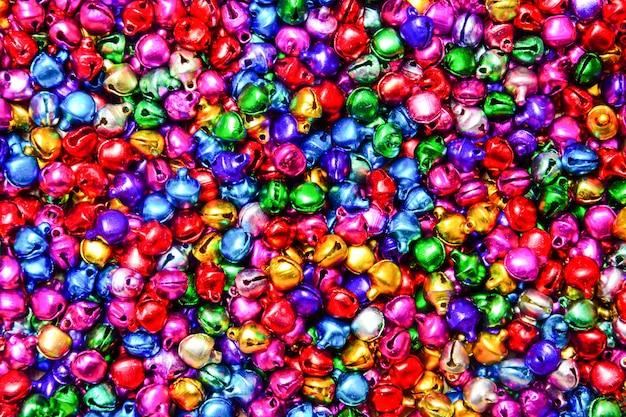 Pilha de sinos coloridos pequenos misturados texturizado fundo Foto Premium