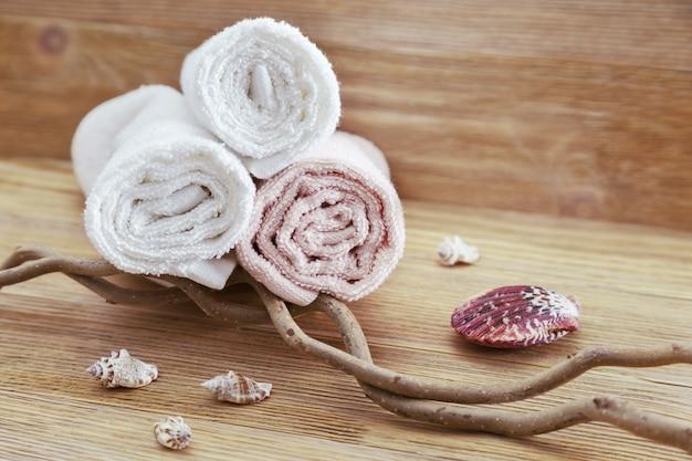 Pilha de toalhas de algodão em fundo de madeira com espaço de cópia. foco seletivo. conceito de spa de itens naturais. Foto Premium