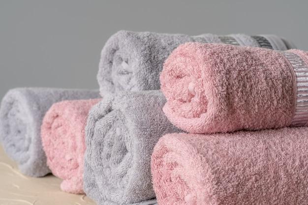 Pilha de toalhas novas e limpas contra parede cinza Foto Premium
