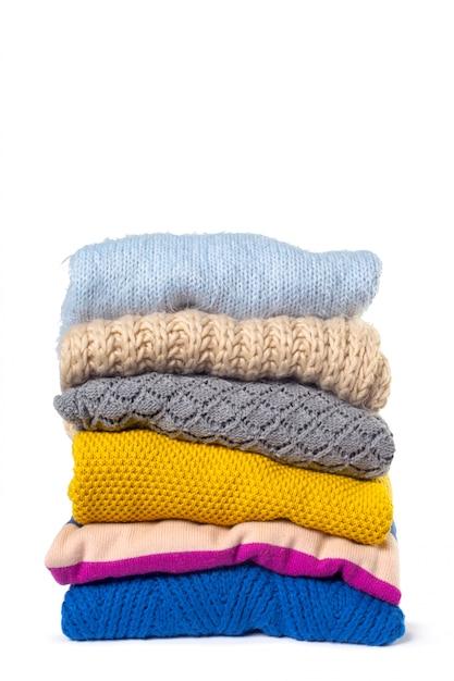 Pilha de várias camisolas isoladas no branco Foto Premium