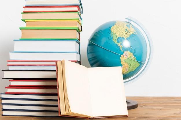 Pilha de vários livros e globo Foto gratuita