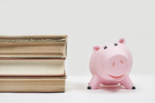 Pilha de velhos livros com mealheiro. custo da educação. economizando dinheiro para a faculdade. economize e pague pela educação infantil na faculdade Foto Premium