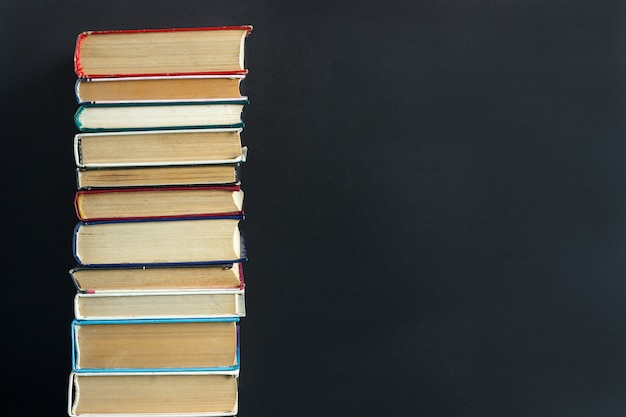Pilha de velhos livros na lousa de fundo preto Foto Premium