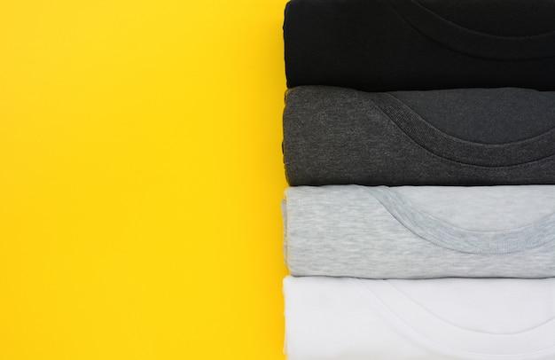 Pilha de vista superior de t-shirt preta, cinza e branca enrolada em amarelo Foto Premium