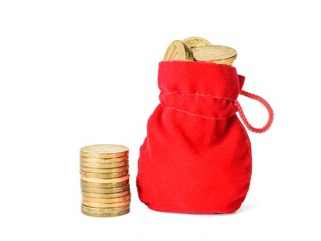 Pilha pequena de moedas e malote com as moedas isoladas no branco. Foto Premium
