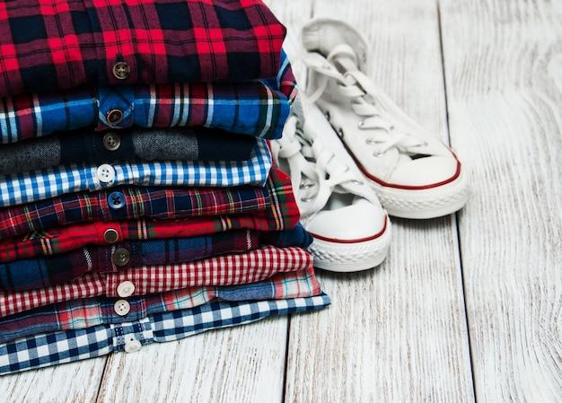 Pilhas de camisas quadriculadas e tênis Foto Premium