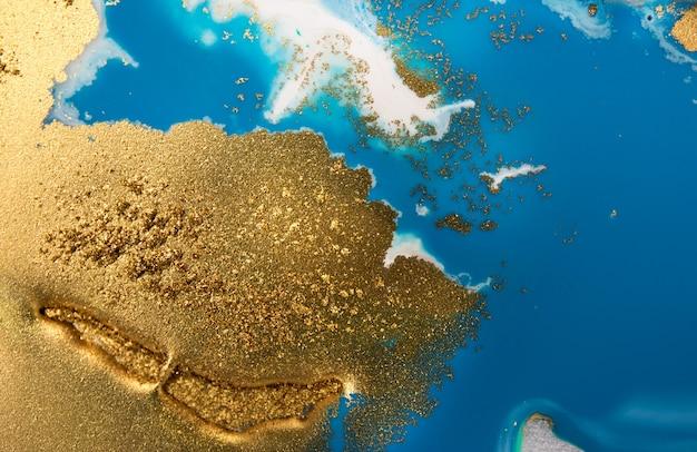 Pilhas de lantejoulas douradas sobre manchas azuis de tinta. derramando tinta abstrata Foto Premium