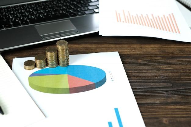 Pilhas de moedas com notebook e gráfico financeiro Foto Premium