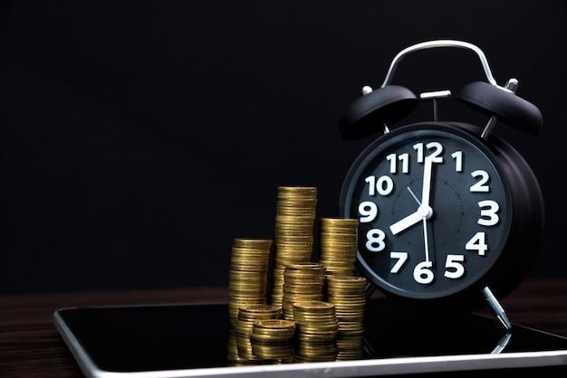 Pilhas de moedas e despertador com computador tablet e gráfico financeiro, visão de planejamento de negócios e conceito de análise de finanças Foto Premium